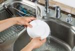 Woman hands washing dinner plate in kitchen sink
