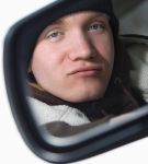 Teen in side view mirror.