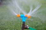 Blue and orange sprinkler watering grass. Garden irrigation system watering lawn. Closeup image of a garden sprinkler on a sunny summer day during watering the green grass in garden.